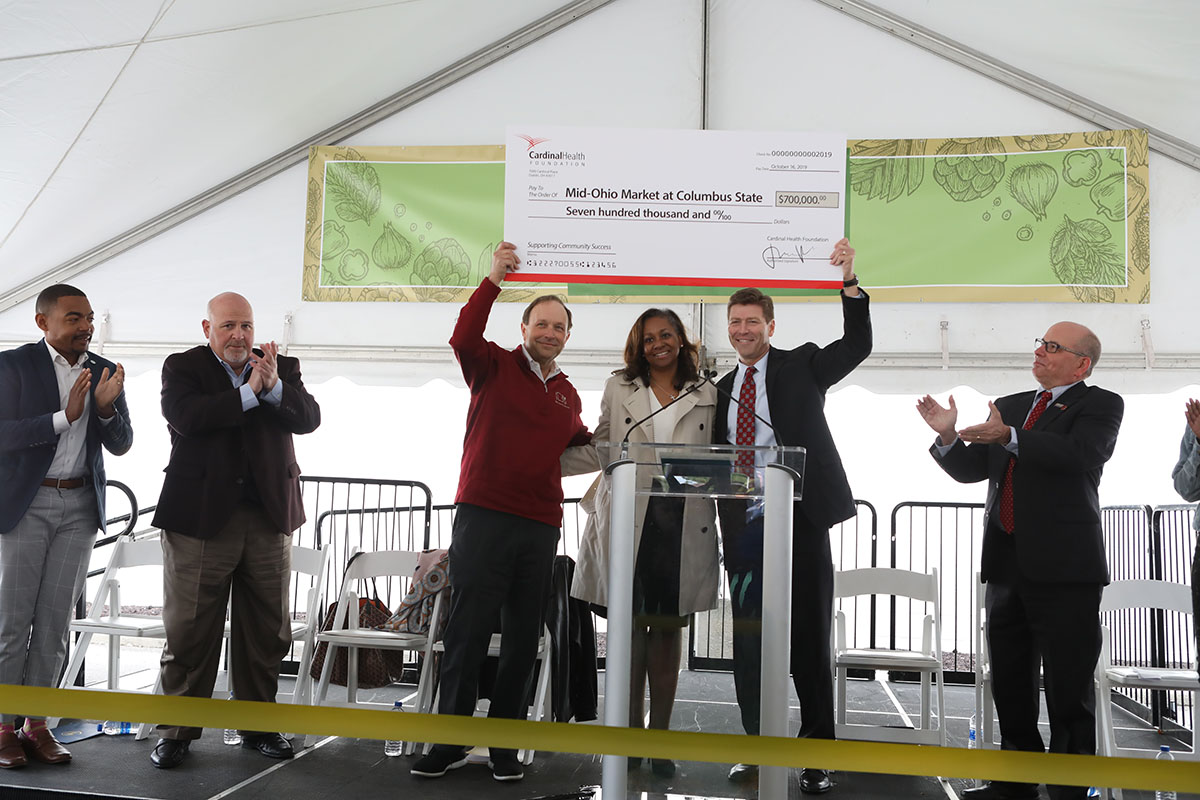 Matt Habash, Mid-Ohio Food Collective, left; Kathryne Reeves, Cardinal Health Foundation Board, center; and Columbus State President David Harrison, right; hold up the $700,000 check at the dedication of the Mid-Ohio Market at Columbus State on October 15, 2019.
