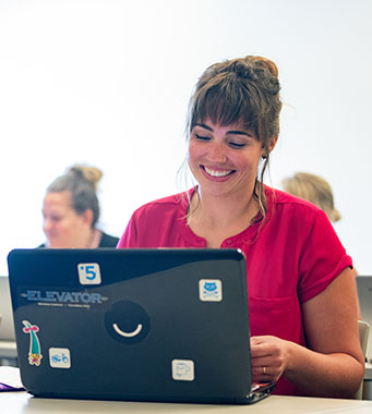 Smiling female computer science student with laptop.