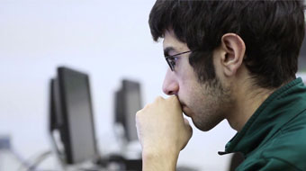Computer Science student in deep thought on computer.