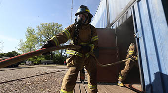 Fire science students practice during live burn simulation.