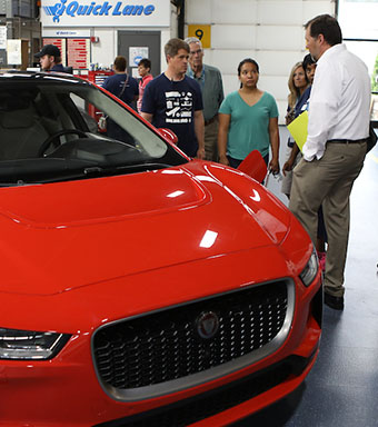 Students looking at red car.