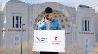 Columbus State student holding preferred pathway sign (Columbus State to Ohio State) in front of the Ohio State University's Horseshoe stadium.