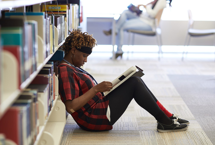 Student sitting on floor in library reading book.